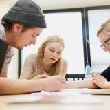 Three Aalto University students are doing group work by writing on paper together.