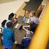 Four Aalto University students working at a table / photo by Unto Rautio