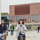 Students riding bikes in front of the Aalto University Väre building, photo by Unto Rautio