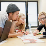 Three Aalto University students lean over a table looking at a laptop screen.