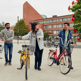 Three people with bikes in front of Väre building