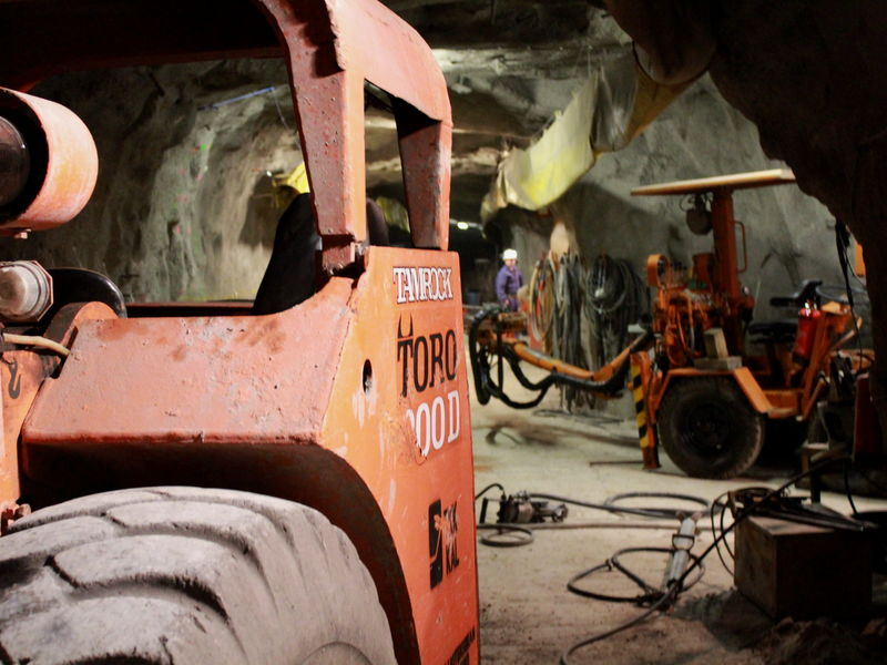 Two work vehicles in an underground tunnel with cables.