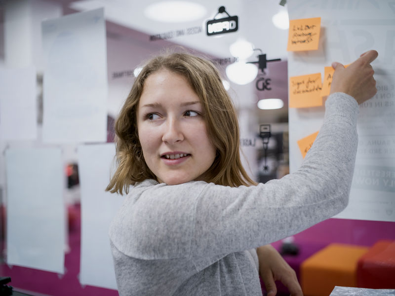 Aalto University student putting post-it notes on a glass wall.