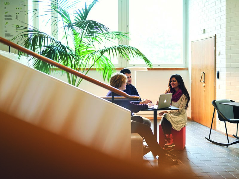 Three people working at a table by a staircase / photo Aalto University, Unto Rautio