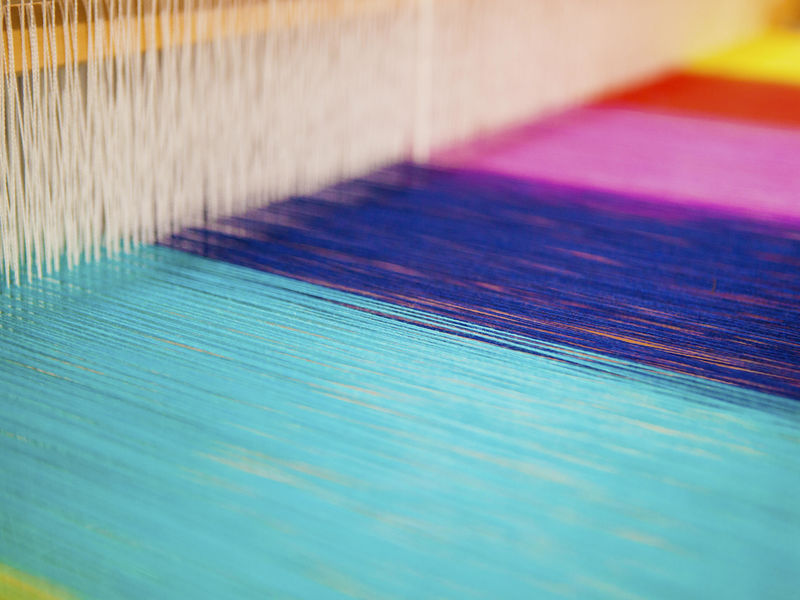 Colourful yarns on a loom in an Aalto University studio facility