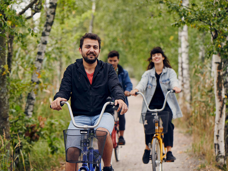 Three happy students biking in Otaniemi