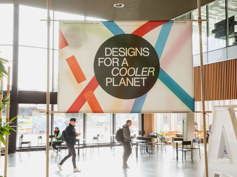 Large banner of the Designs for a Cooler Planet event with a few people walking around it