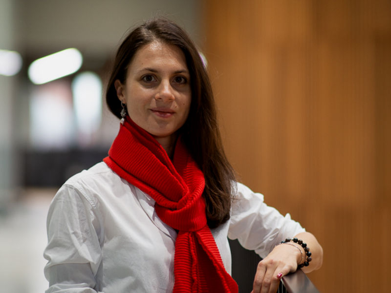Picture of Lidia Borisova She is wearing a white shirt and red scarf and is smiling towards the camera.