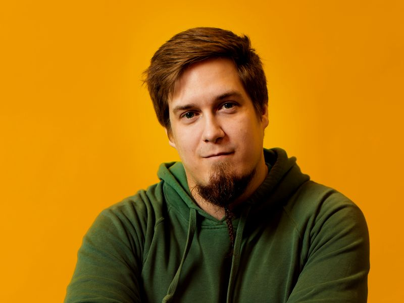 Picture of Simo Lahdenne in a darkgreen hoodie towards an orange background. He has crossed arms and is looking into the camera.