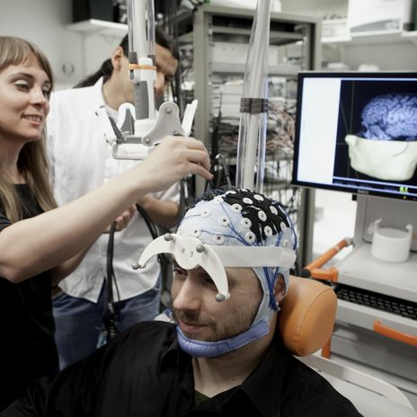 Researcher setting braing imaging receptors to a voluntary subject