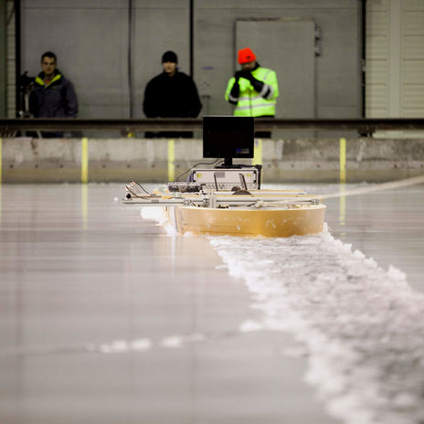 Three researchers using a device on the surface of the ice at Aalto ice tank