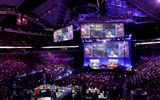 Large arena filled with a crowd watching a game of DOTA2 projected on big screens