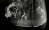 black and white photograph of artist Yo-Yo Lin performing on a stage with right knee and her left hand touching the floor. She is surrounded by a translucent scrim with graphical images projected upon it.