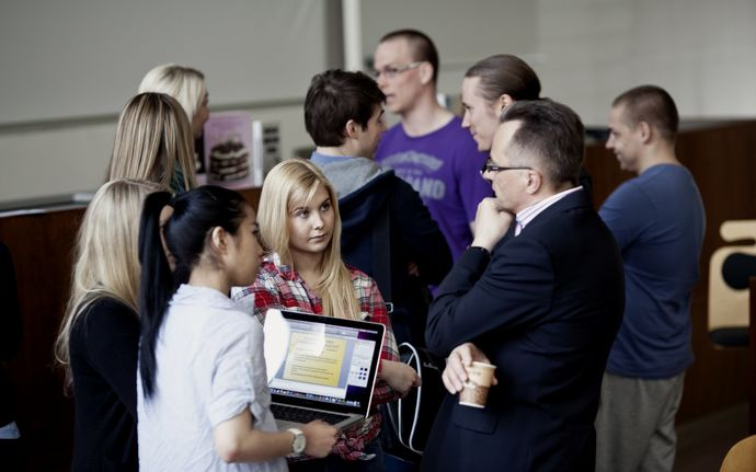 Two business students, one is holding a laptop, discussing with the Professor after his lecture. Another group of students talk in the background.