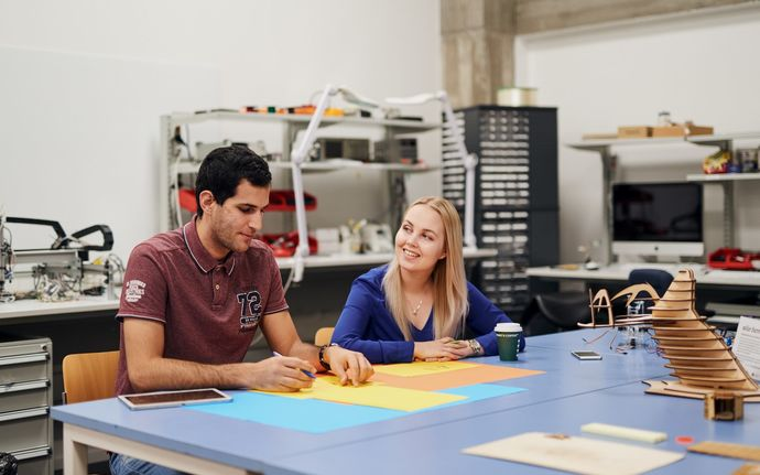 Two students drawing on coloured paper at a table in a workshop space