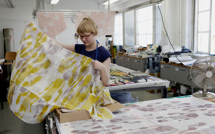 Student holds up a piece of printed fabric in the Textile printing workshop in Väre