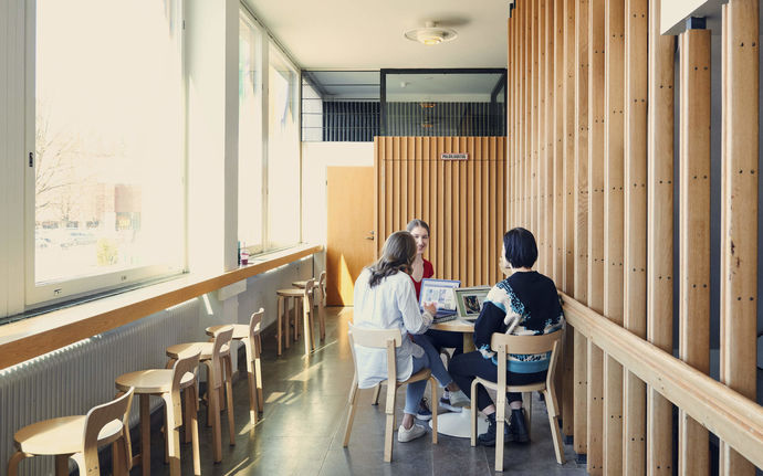 Three students sitting around a Alvar Aalto classic table in the Otakaari 1 caféteria / photo by Unto Rautio