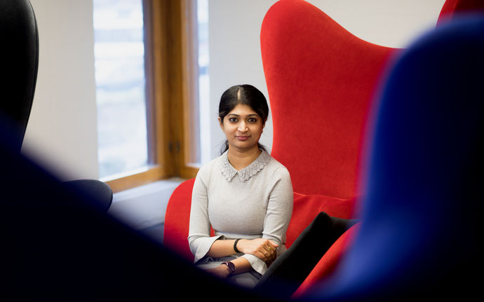Nagadivya Balasubramaniam sitting on a red armchair