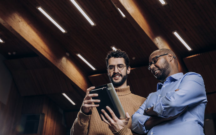 Two Aalto students or employees viewing materials from a tablet, photo by Aleksi Poutanen