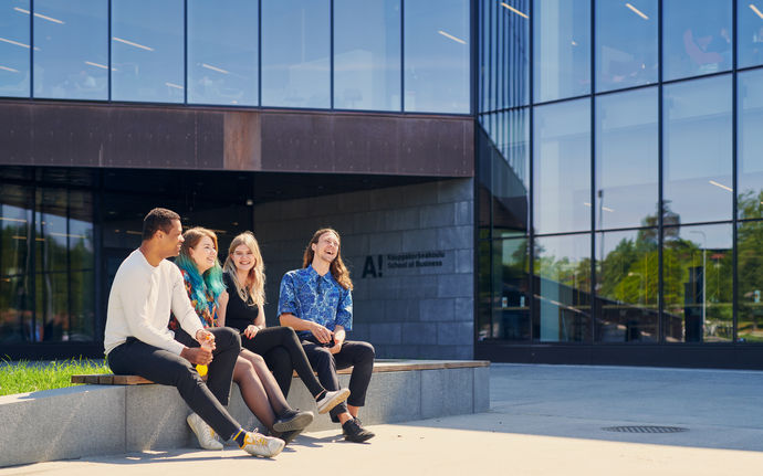 Picture of students sitting in front of the School of Business