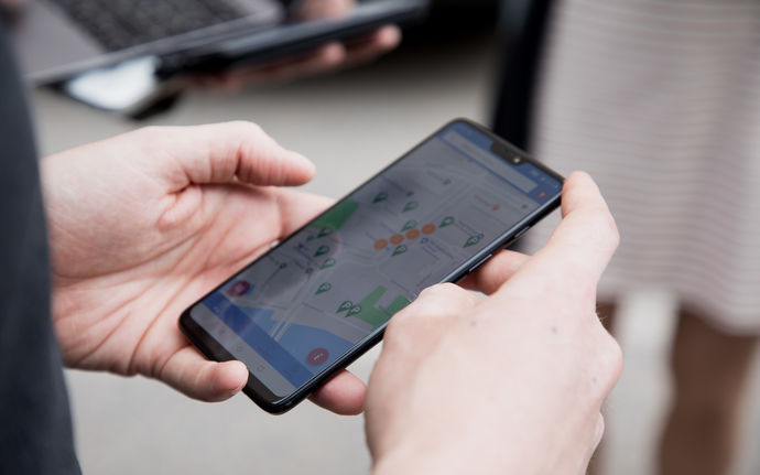 Hands holding a smartphone that displays a map application