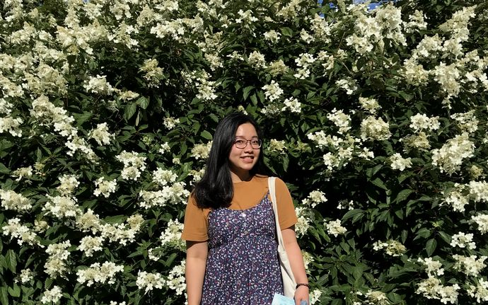 Linh standing in front of a flower wall smiling
