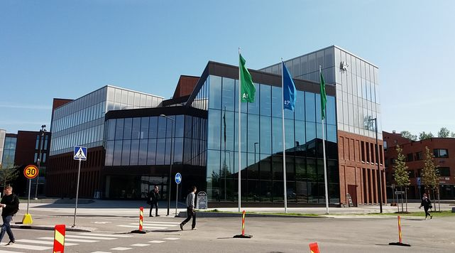 Outside picture of the School of Business building in Otaniemi. Three Aalto Flags swinging in front of the building.