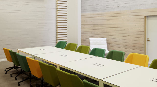 Long, white table surrounded by 20 chairs in light and dark green and yellow. Backdrop is white concrete wall with some birch cladding. Photo by Aalto University / Tuomas Uusheimo