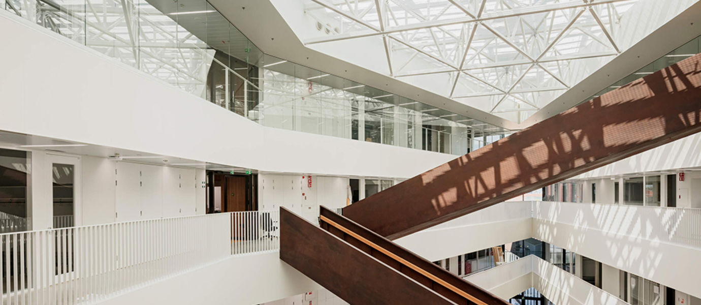 Väre building in the campus. Inside shot of natural light filled dark wood staircase criss-crossing in white surroundings. Light through skylights. Photo by Aalto University / Tuomas Uusheimo