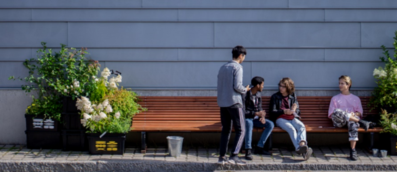 Two students talking to two festival visitors who are sitting on a bench.