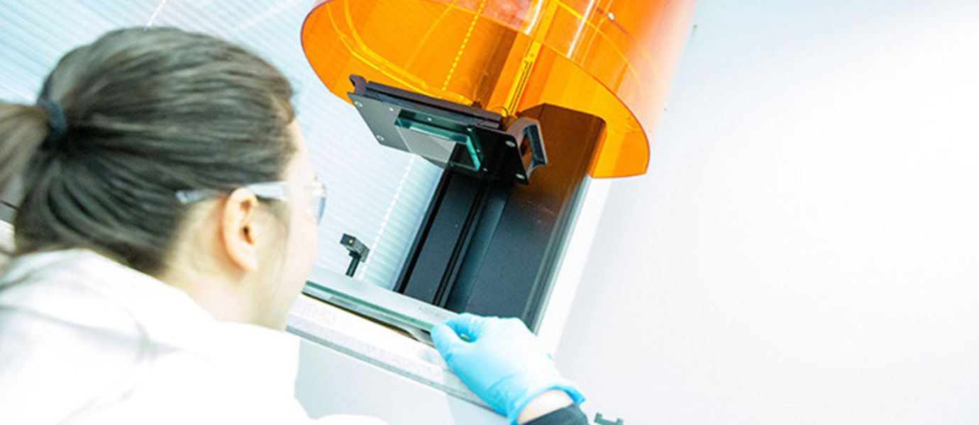 Health and Wellness researcher looking at a 3D printer from below