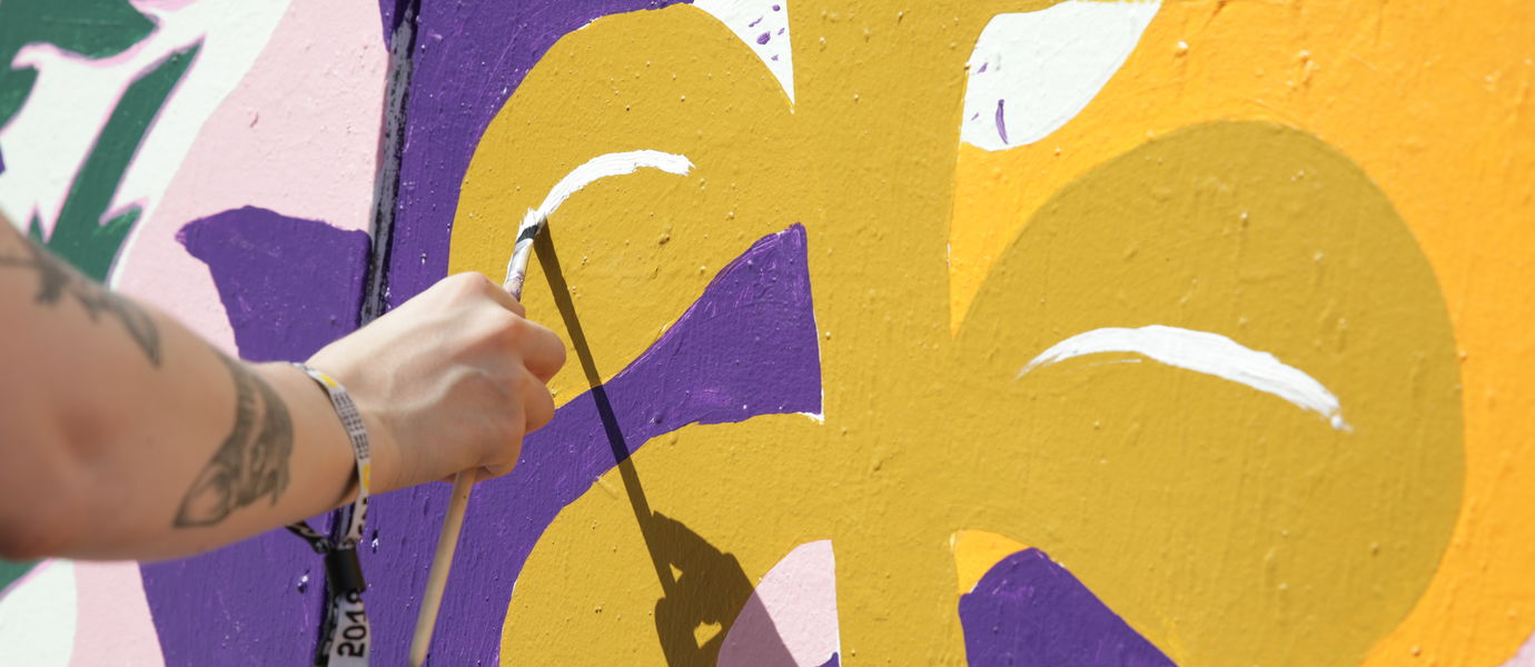 Juliana Hyrri painting a mural at Flow Festival