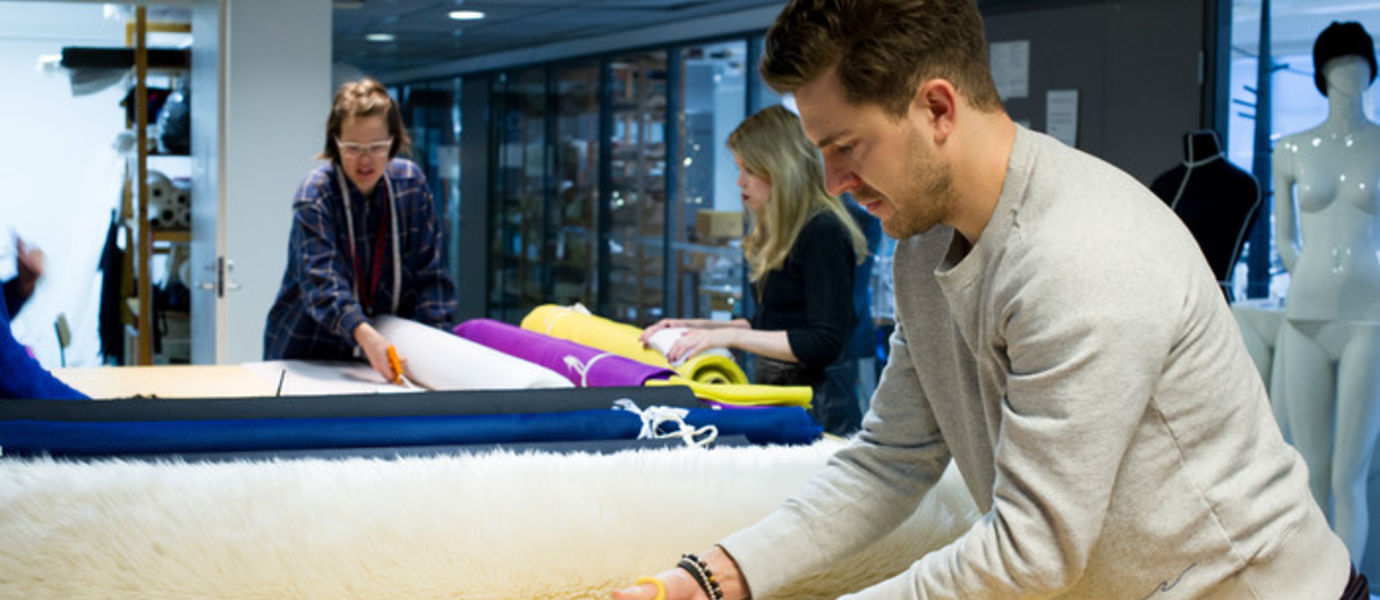 A man cutting fabric in the sewing workshop at Aalto University
