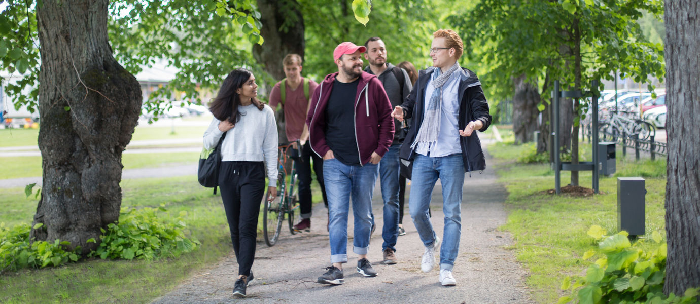 Aalto University / group of students walking under trees / photography: Roee Cohen