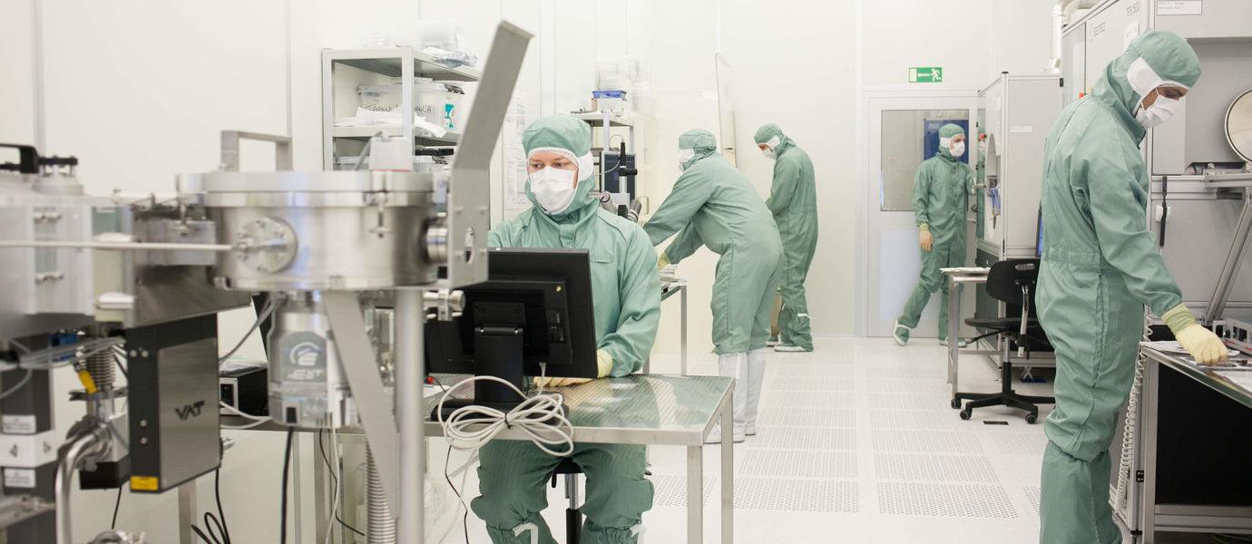 Three people in clean room laboratory