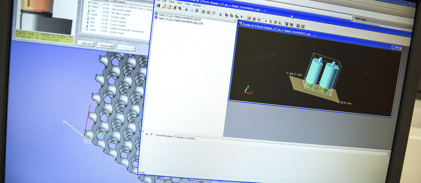 Computer screen with several windows open, showing cylindrical shapes on topmost windoe and three-dimensional grid structure underneath it. Photo by Mikko Raskinen.
