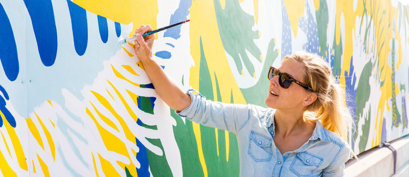 A girl with sunglasses paints a wall at Flow festival site