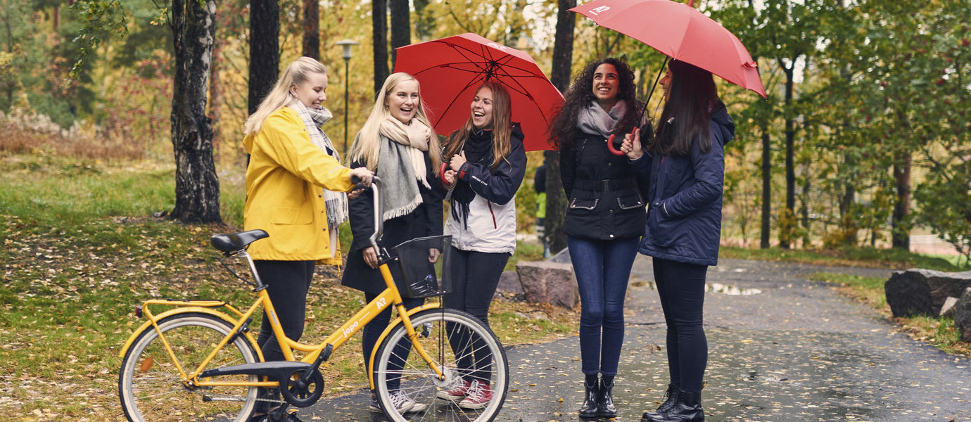 Five students standing in the rain. One has a bike and two have a red umbrella.