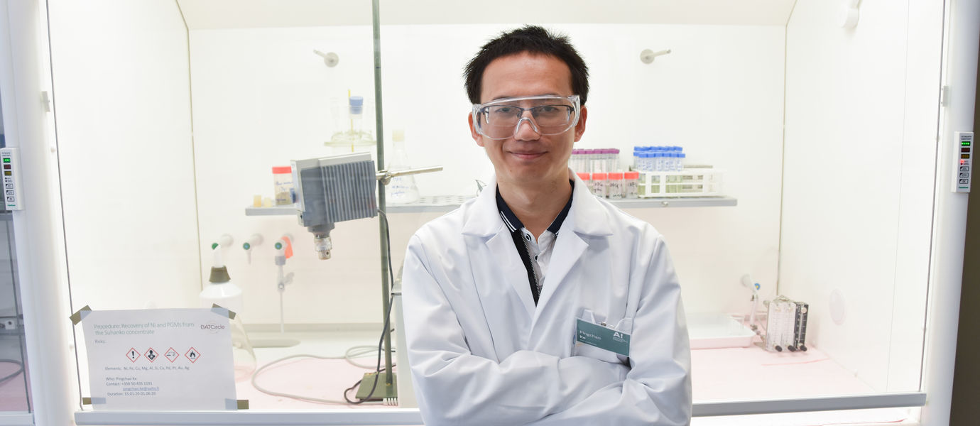 Pingchao Ke in the laboratory with safety gear standing in front of lab equipment smiling