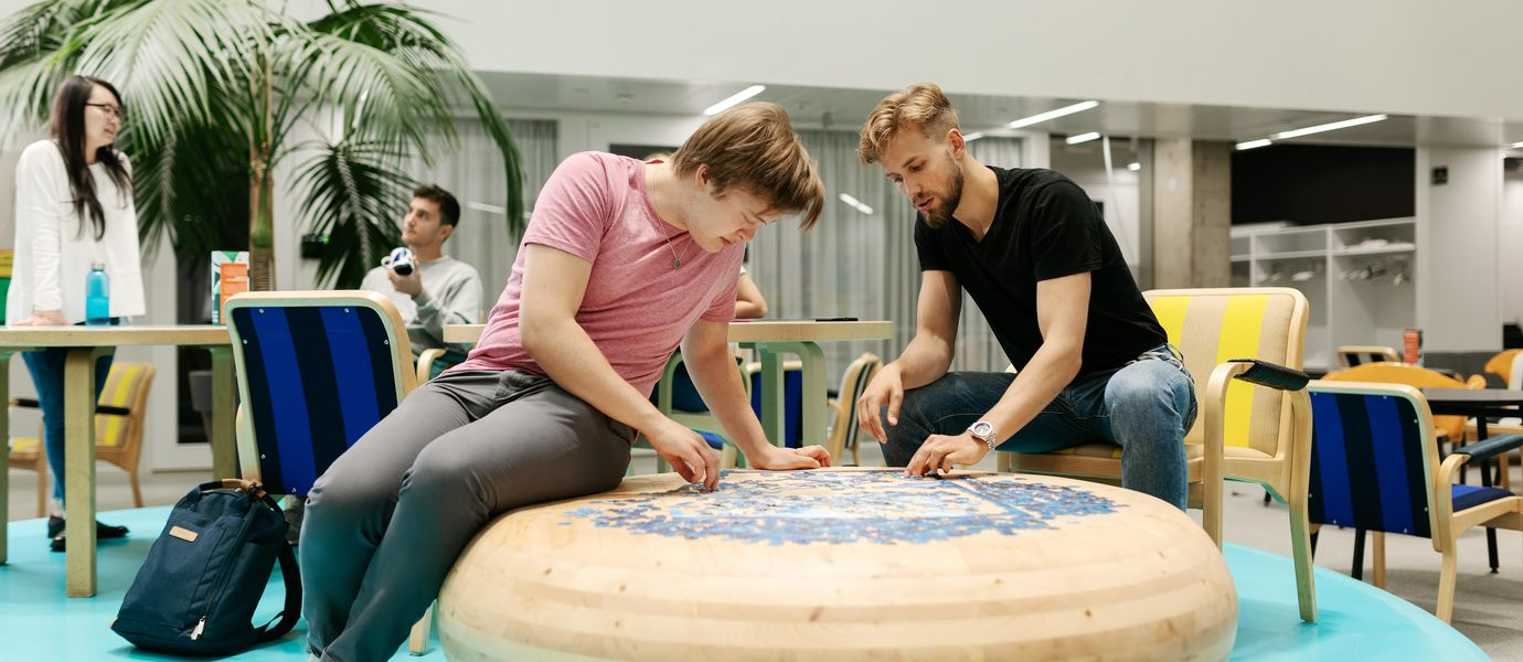 Students sitting by an interesting wooden table doing a puzzle