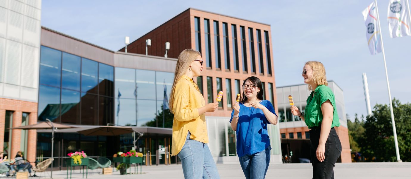 Three women talking and eating ice cream in front of the Väre building.
