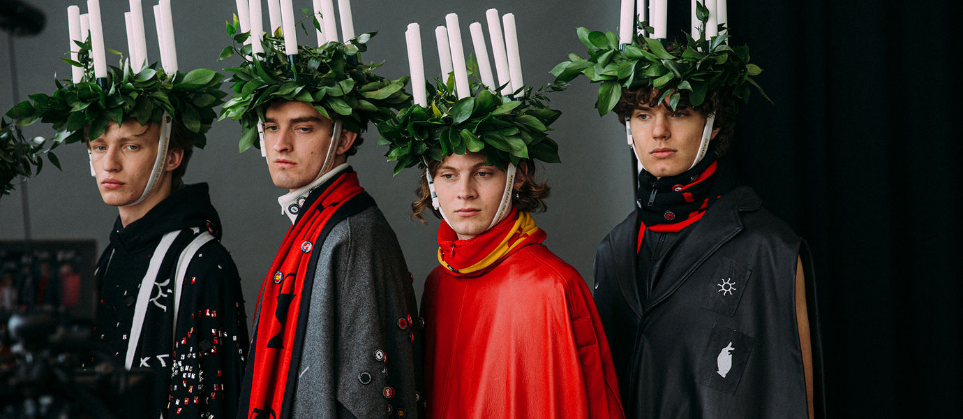 three models wearing candle headpieces and capes