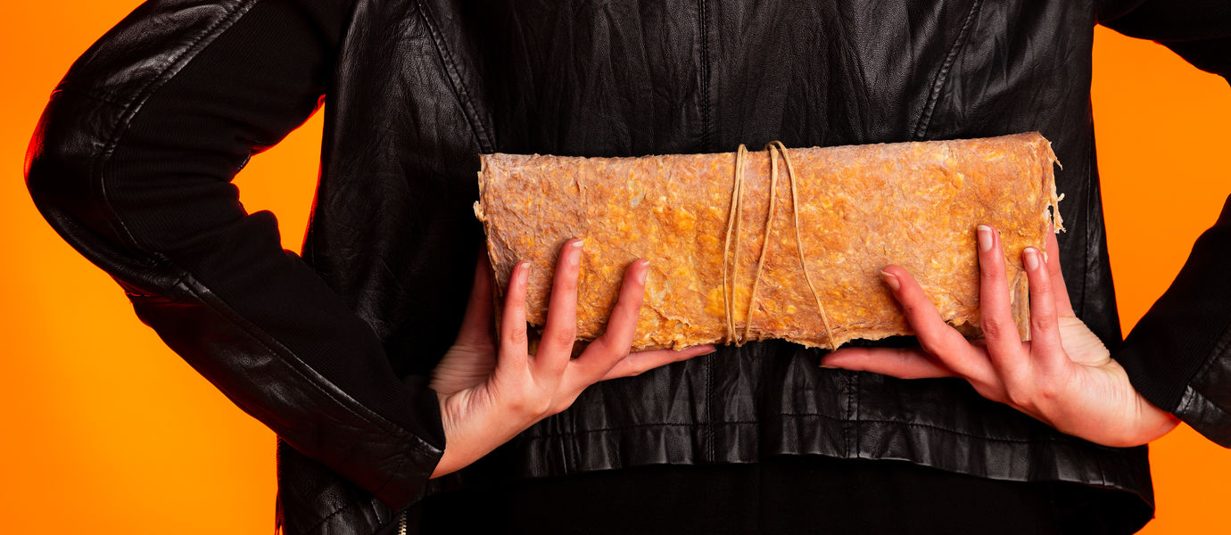 A person wearing a leather jacket with their back to the camera in front of an orange background, holding a clutch bag made of biomaterials behind their back.