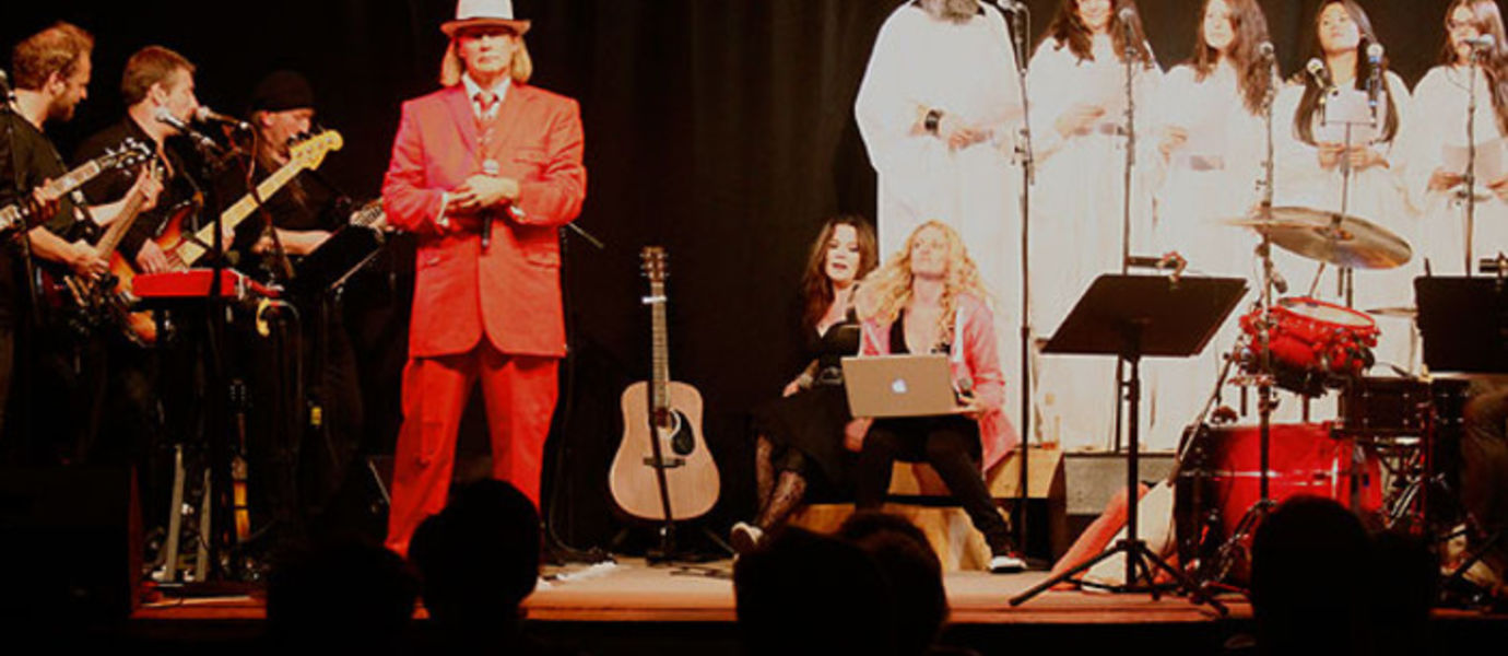 Playing God show, Matti Häyry in the middle with his red suit as the crooked science merchant in the opera.