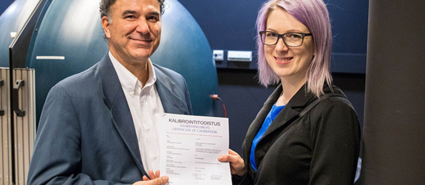 Development Manager Anne Ala-Pöntiö of Orion Diagnostica Oy receives the 1000th calibration certificate from Head of Calibration Services, Dr. Farshid Manoocheri