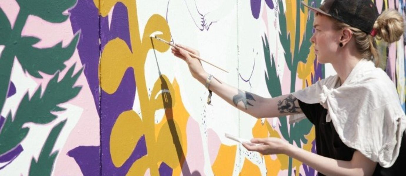 Students illustrate a 100 meters mural wall for Flow. Juliana Hyrri painting. Photo: Aalto University.