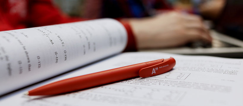 Close-up of a red Aalto pen lying on a spread of an engineering book, students studying in the background / photo by Aalto University, Aino Huovio