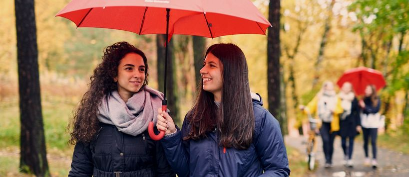 Two Aalto University alumni walks outside under a red Aalto umbrella
