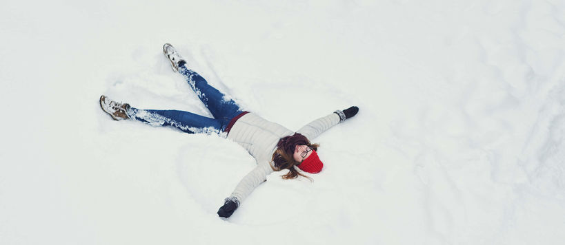 Student lying on snow, making stars. Photo by Aalto University / Unto Rautio