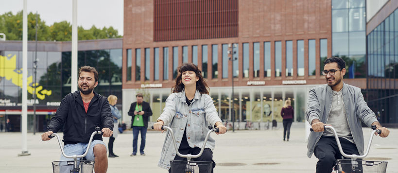 Thre students bicycling in front of the Väre building.